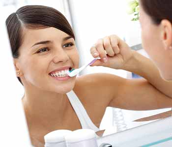 Image of a young Lady brushing her teeth to cure from gum disease