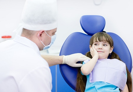 child in tooth pain at the dentist